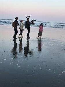 people filming on a beach