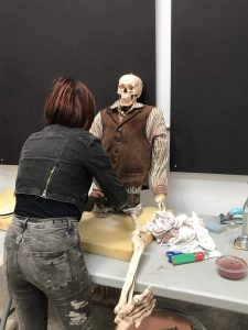 A lady dressing a skeleton